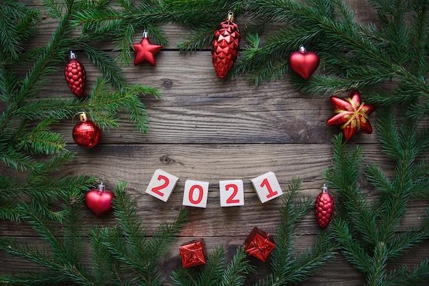 Beau cadre de branches d'arbres de noël avec des jouets et numéro 2021. fond de bonne année