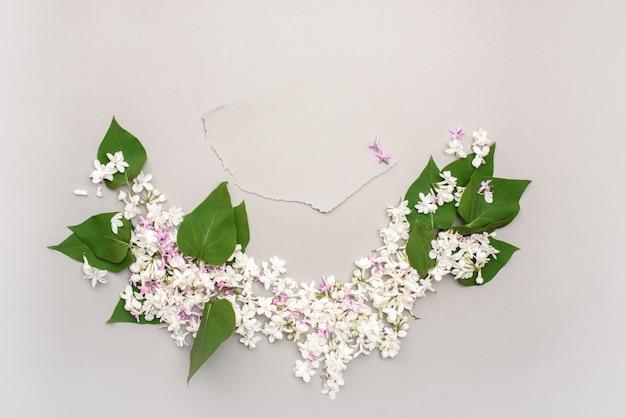 Un beau cadre de feuilles vertes et de fleurs lilas blanches sur fond gris, avec une carte postale grise pour le texte.