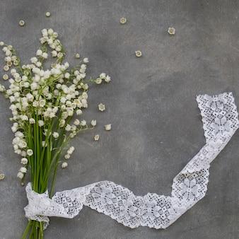 Beau cadre floral avec des fleurs de lys de la vallée sur un fond gris foncé