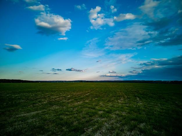Beau champ agricole vert de paysage de campagne et ciel bleu profond avec les nuages blancs
