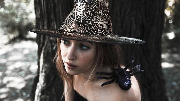 Beau charmeur avec une araignée sur l'épaule dans les bois ensoleillés