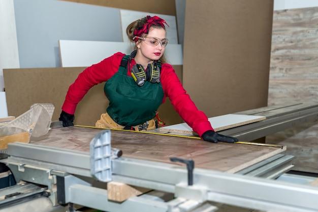 Beau charpentier faisant des mesures de planche de bois