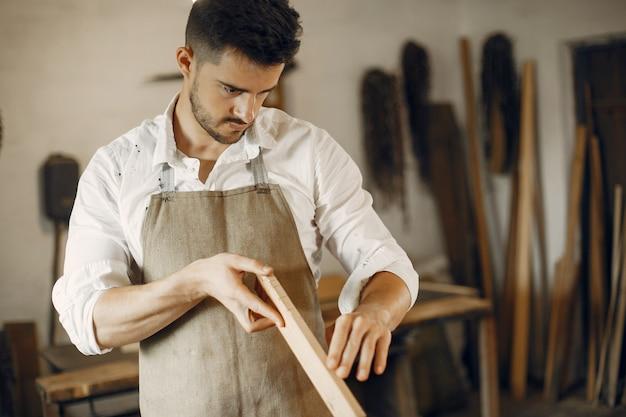 Beau charpentier travaillant avec un bois