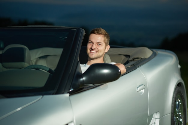 Beau chauffeur de cabriolet argenté souriant.
