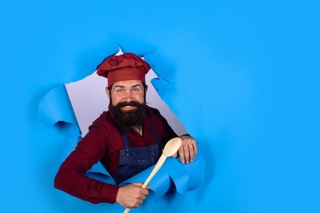 Beau chef cuisinier avec cuillère en bois regardant à travers le papier chef homme en uniforme de cuisinier détient en bois