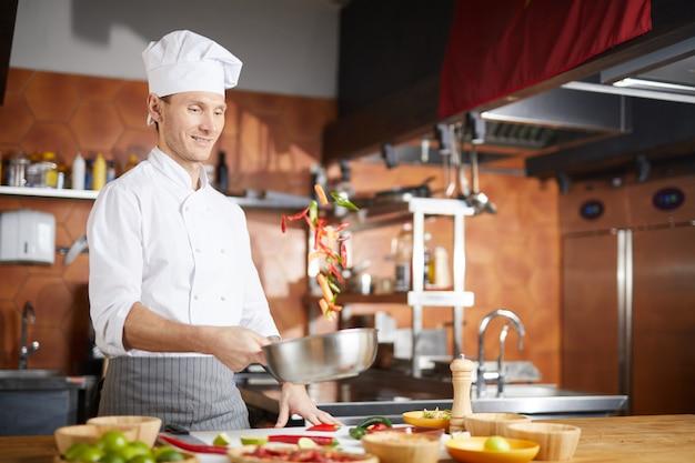 Beau chef cuisinier de légumes