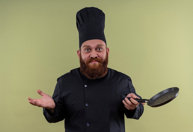 Un beau chef homme en uniforme noir tenant une poêle à frire avec la main ouverte sur un mur vert