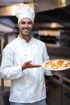 Beau chef présentant une pizza