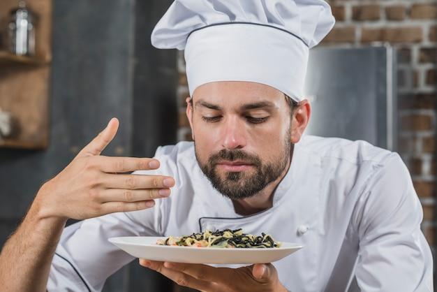 Beau chef reniflant l'odeur du plat cuisiné