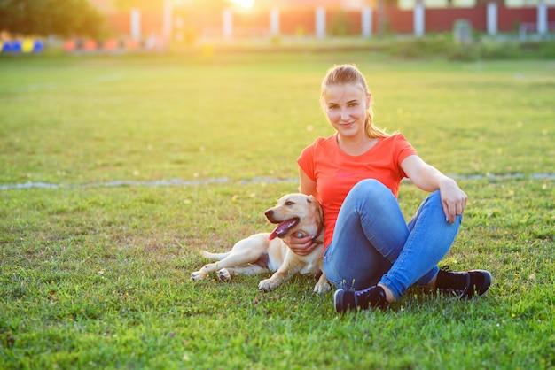 Beau chiot labrador jouant sur la pelouse avec youn girl au coucher ou au lever du soleil