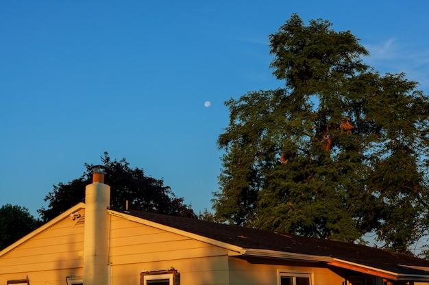 Beau ciel bleu et lune au-dessus du toit de la maison
