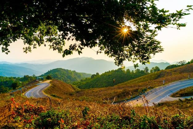 Beau ciel coucher de soleil avec couche montagne et route