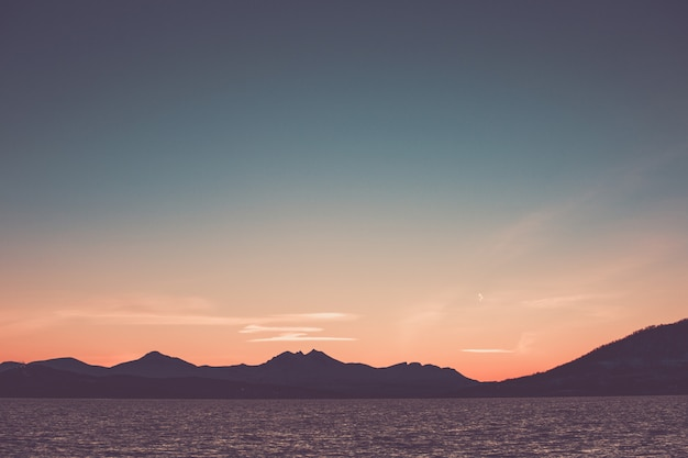 Beau ciel de coucher de soleil rose sur la silhourtte des montagnes au bord de la mer.