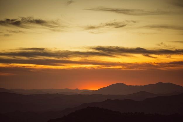 Beau ciel sur les tons jaunes avec des montagnes