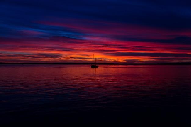 Beau cliché du coucher de soleil au bord de la mer avec un bateau au milieu