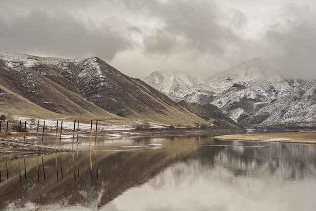 Beau cliché de la mer reflétant les montagnes sous un ciel nuageux