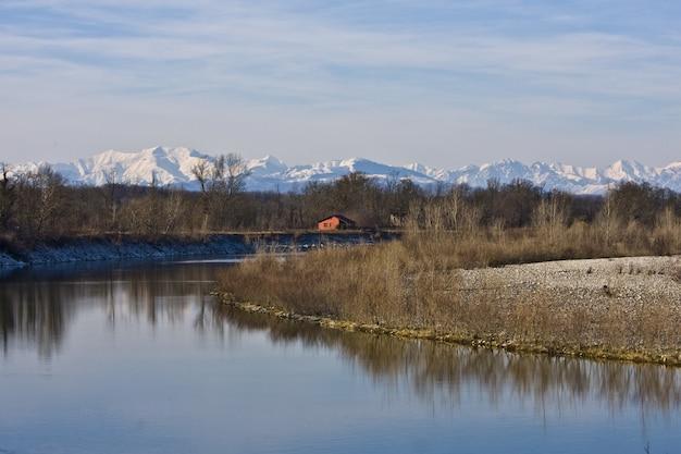 Beau cliché d'une rivière au milieu des rives et des arbres sans feuilles avec une maison au loin