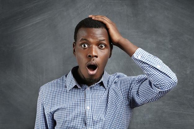 Beau client africain aux yeux d'insectes ayant une expression oublieuse, tenant la main sur sa tête, gardant la bouche grande ouverte, l'air surpris et effrayé, se souvenant soudainement des grosses ventes dans les magasins