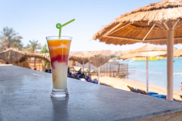 Un beau cocktail de fruits tricolore dans un verre sur une table en bois sur fond de ciel ensoleillé et de plage de sable.