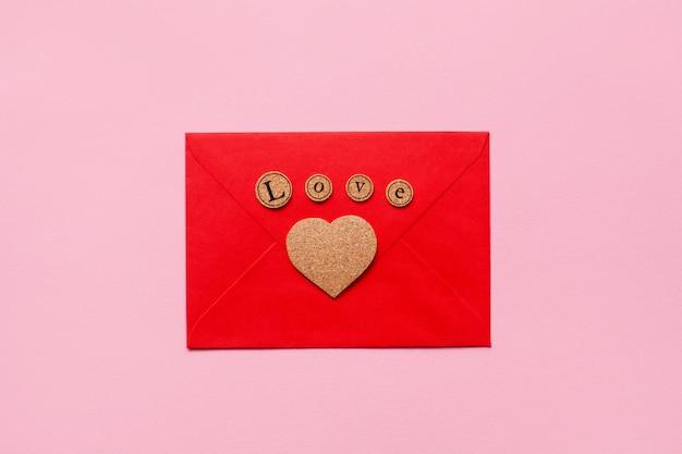 Beau coeur en bois et lettres d'amour sur une enveloppe en papier rouge