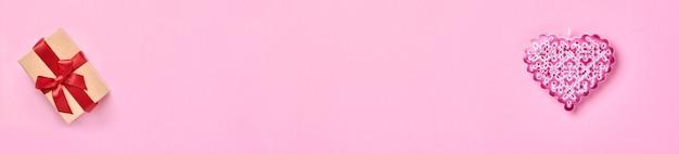 Beau coeur décoratif ajouré et coffret cadeau avec ruban rouge sur un mur de table rose.