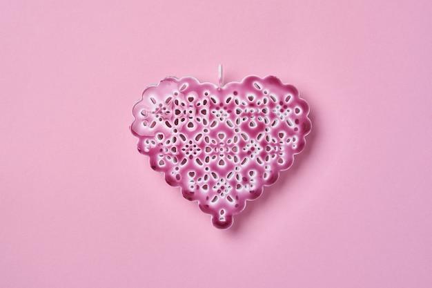 Beau coeur décoratif ajouré sur un mur de fond rose. carte de voeux saint valentin. vue de dessus.