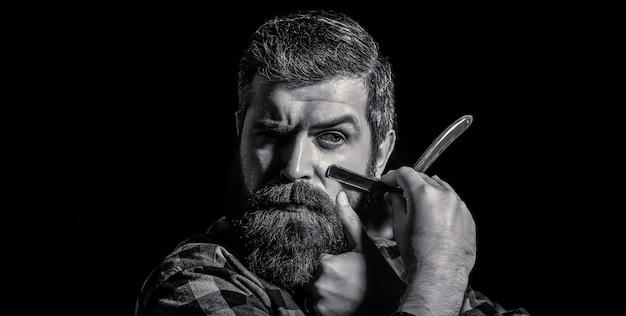 Beau coiffeur barbu tient un rasoir droit tandis que le salon de coiffure rasoir droit