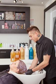 Beau coiffeur tonifiant les cheveux du client dans le salon