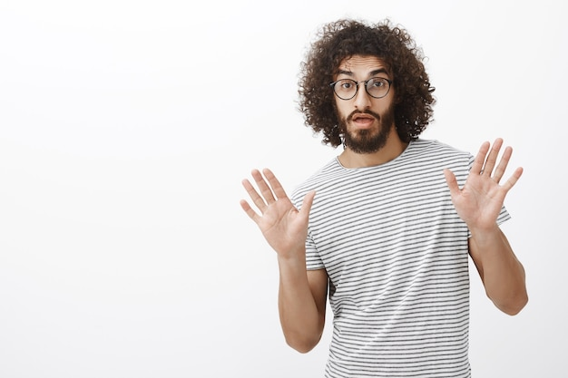 Beau collègue masculin barbu hispanique créatif avec une coiffure élégante, levant les paumes tout en façonnant quelque chose pendant la conversation