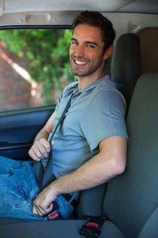 Beau conducteur attachant la ceinture de sécurité