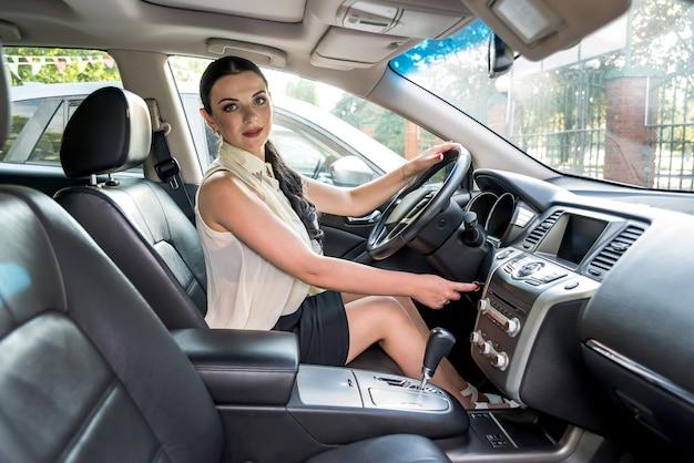 Beau conducteur avec clé de voiture posant à l'intérieur
