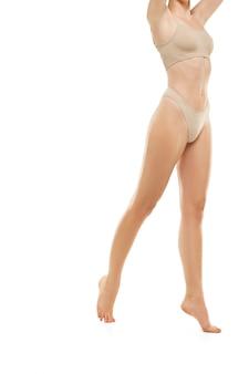 Beau corps féminin isolé sur fond de studio blanc