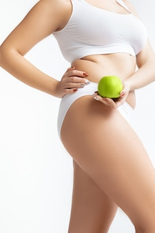 Beau corps féminin en sous-vêtements isolé sur mur blanc