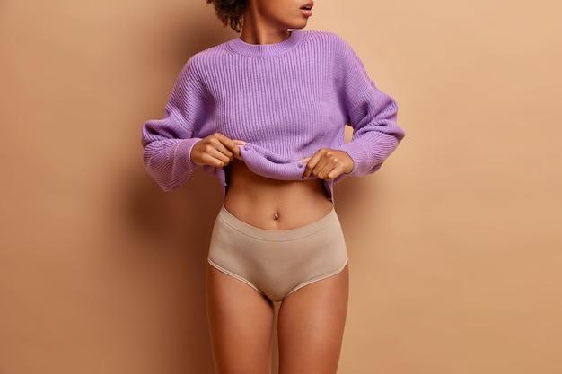 Beau corps de femme mince. une femme en forme enlève un pull violet montre que son ventre plat porte une culotte a une peau saine