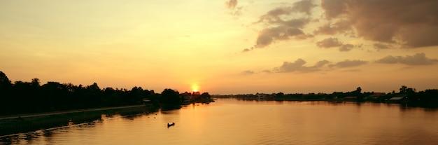 Beau coucher de soleil au-dessus de la rivière rurale avec pêcheur en bateau