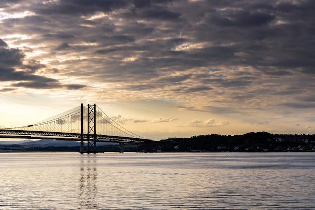 Beau coucher de soleil au pont de la route du forth et pont de passage de queensferry édimbourg