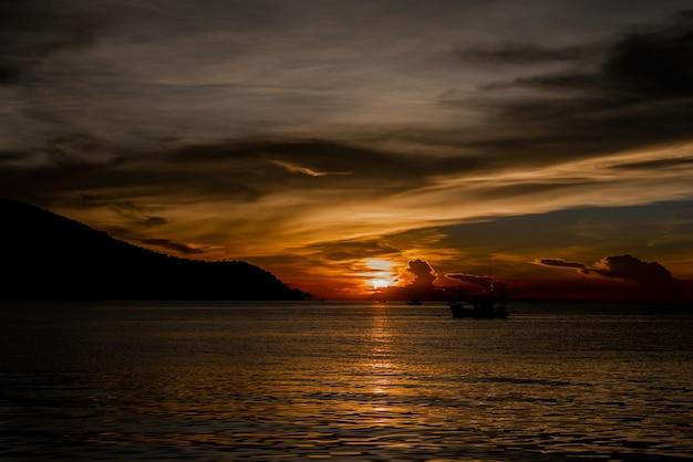 Beau coucher de soleil et un bateau à la mer