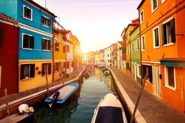 Beau coucher de soleil avec bateaux, bâtiments et eau. lumière du soleil. toning. burano, italie.