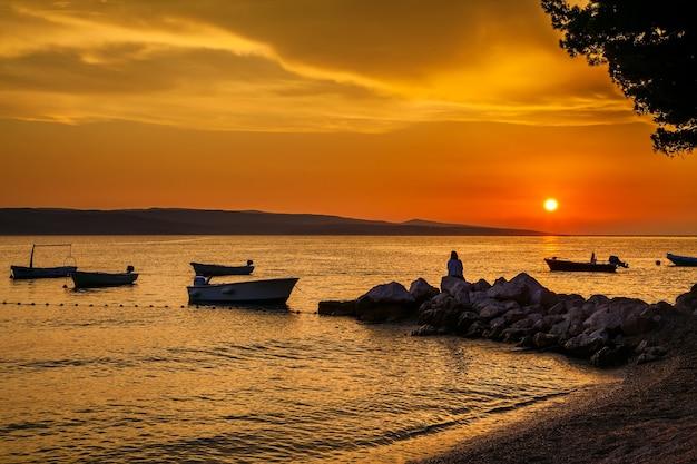 Beau coucher de soleil avec les bateaux et femme assise sur les pierres, croatie