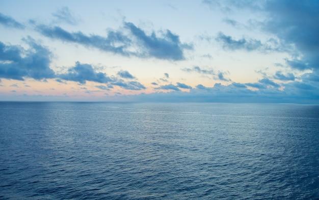 Beau coucher de soleil et chemin d'argent sur la mer, nuages bleus dans le ciel, fond