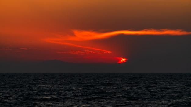 Beau coucher de soleil coloré à la mer avec des nuages et des montagnes dramatiques