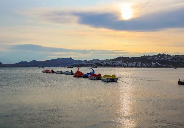 Beau coucher de soleil sur la côte égéenne avec des îles et des montagnes bateaux et catamarans