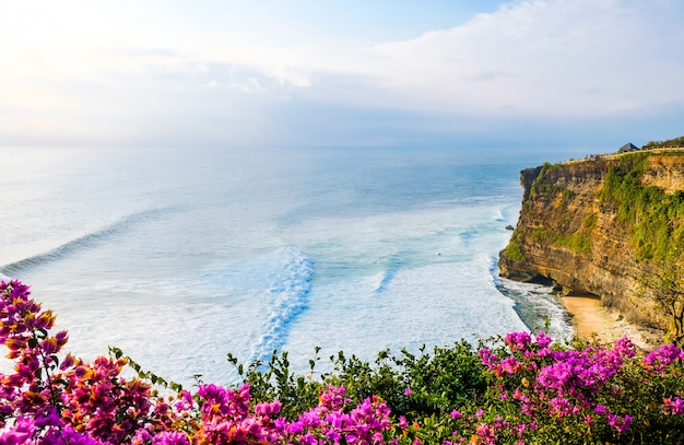 Beau coucher de soleil sur la côte de l'océan près du temple uluwatu, bali, indonésie. fleurs sur les vagues de la mer au coucher du soleil.