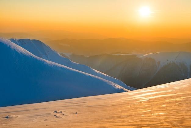 Beau coucher de soleil dans les montagnes d'hiver couvertes de neige. paysage nature