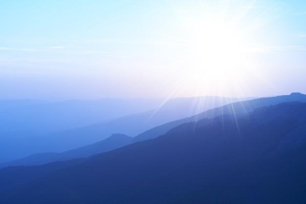 Beau coucher de soleil dans les montagnes. paysage coloré avec soleil et ciel bleu