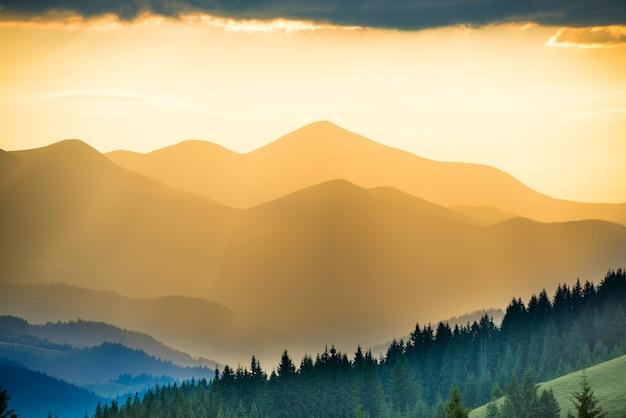 Beau coucher de soleil dans les montagnes. paysage avec soleil qui brille à travers les nuages orange