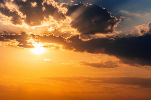 Beau coucher de soleil doré dans le ciel avec les rayons du soleil à travers les nuages