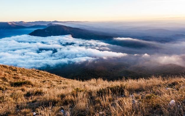 Beau coucher de soleil doré dans les montagnes avec des nuages bas.