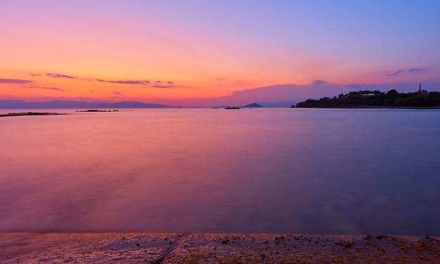 Beau coucher de soleil sur le golfe saronique de la mer égée sur l'île d'égine, grèce - coucher de soleil paysage - paysage marin. longue exposition, l'eau est totalement brouillée par le mouvement