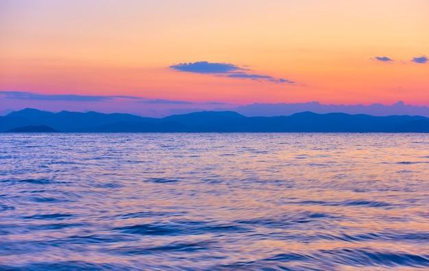 Beau coucher de soleil sur le golfe saronique de la mer égée sur l'île d'égine, grèce - paysage au coucher du soleil